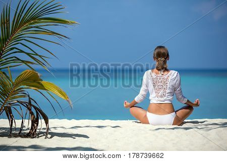 Beautiful girl sits in a pose of a lotus and meditates on the coast Maldives.