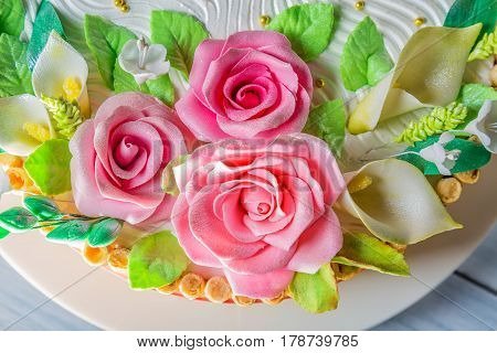Delicious cake with roses lily and leaves on light blue wooden table close up with selective focus.