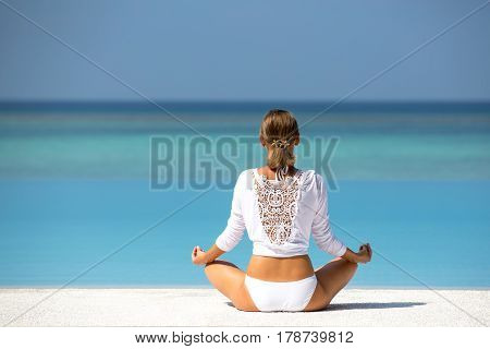 Young woman practicing yoga on the beach Maldives.