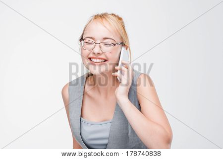 Young smiling blonde in glasses extremely happy, joyful and pleased talking on phone. Positive emotions, happiness, jubilation and gladness. Grey background with copy space.