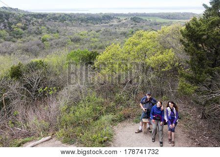 DALLAS, TEXAS, MARCH 16. The Cedar Ridge Preserve on March 16, 2017, in Dallas, Texas. A Trio of Hikers at the Cedar Ridge Preserve managed by Audubon in Dallas, Texas.