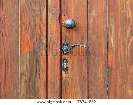 old wooden door with cracked paint and old decorative crank