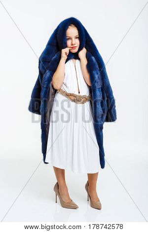 Nice girl in fashion white dress covering head with fur as it is a hood.