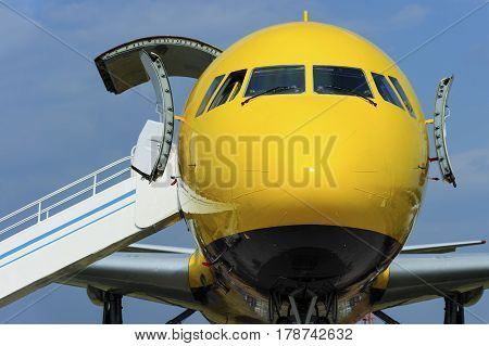 Yellow passenger plane with opened door and ramp near entrance in airplane, aviation and aerospace industry, blue sky on background