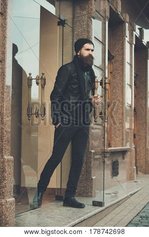 Serious Bearded Man Hipster Exit Glass Door In Leather Jacket
