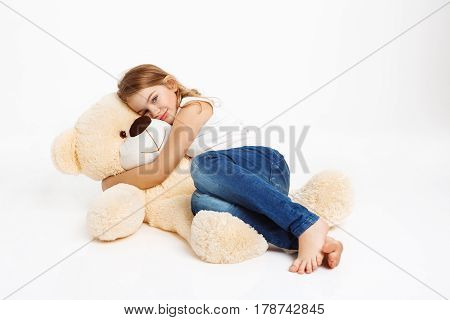 Little nice girl lying on floor, hugging favourite teddy bear, looking straight at camera.