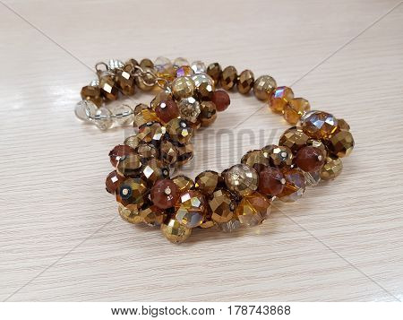 Golden beads necklace on the wooden table