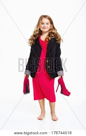 Cheerful long haired girl wearing mommy's dress and jacket, holding high heels shoes. White background.