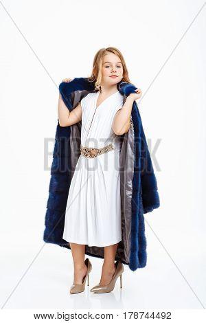 Charming little girl in amazing white evening dress taking off dark fur coat. White background.