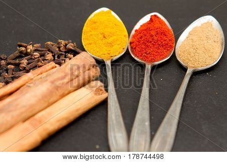 A collection of spices on three spoons