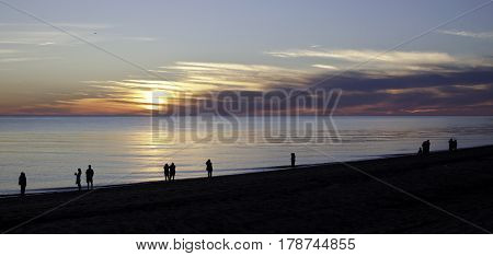 Panorama view of a beautiful red/orange sunset with clouds over the blues of the North Atlantic highlights people in silhouette along the shoreline of Race Point Beach, Provincetown, Cape Cod, Massachusetts as the last light of sunset falls in mid Septemb