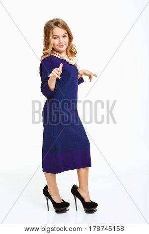 Nice girl wearing mother's tank dress, shoes, white bead necklace, looking at camera. White background.