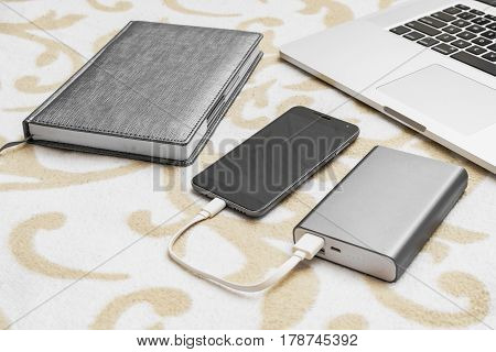 Computer And Notebook With Cell Phone Charge From Power Bank On Sofa