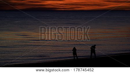 A brilliant red sunset with clouds over the North Atlantic highlights two figures in silhouette at the shoreline of Race Point Beach, Provincetown, Cape Cod, Massachusetts as the last light of sunset falls in mid September.