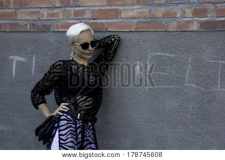 A young caucasian female leans on her arm against a wall