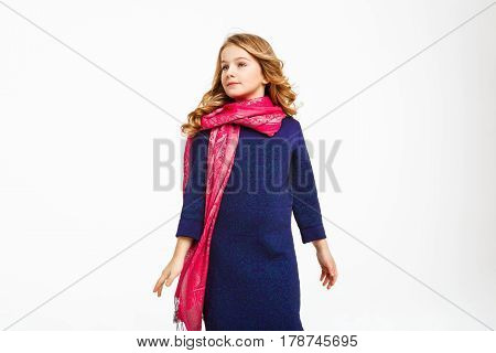 Closeup of chaming little girl in elegant dress and stylish scarf looking away, smiling.