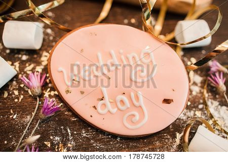 Wedding day background. Sweets for decoration. Handmade wedding cookie decorated with lettering on wooden surface closeup.