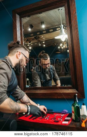 Barber preparing instruments for work free space. Senior bearded hairtician check work tools for haircut at his workplace against mirror. Barbershop concept
