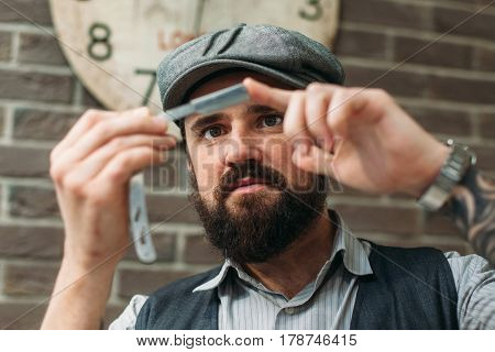 Barber check sharpness of razor closeup. Portrait of young bearded man touching cutthroat. Shaving, grooming, beauty, style, face care concept