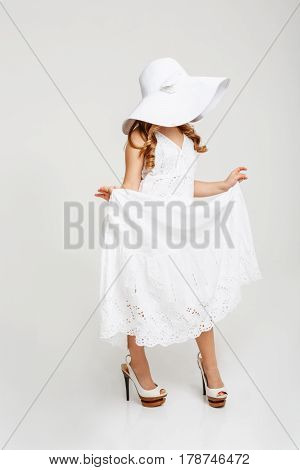 Side view of little girl in nice summer clothes, holding out lacy dress. White background.