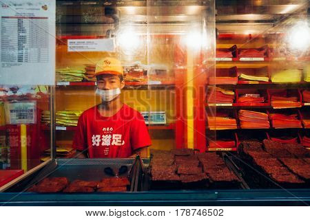 KUALA LUMPUR MALAYSIA - MARCH 17: Young man sells chinese dried meat (Bakkwa) at the street food stall in Chinatown Kuala Lumpur Malaysia on March 17 2016.