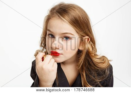 Closeup portrat of cheerful kid making up, copying mother's behaviour. Putting lipstick on, looking straight.