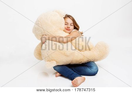 Cheerful kid sitting on floor holding toy bear on knees, hugging it with eyes closed.