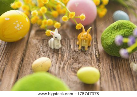 Rabbits With Easter Eggs On Wooden Table. Cute Little Easter Bunny