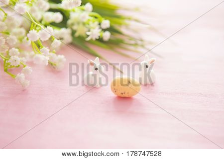 Easter Eggs And Flowers With Bunny Statuettes On Wooden Background