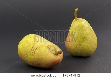 two ripe scratched pears black isolated closeup