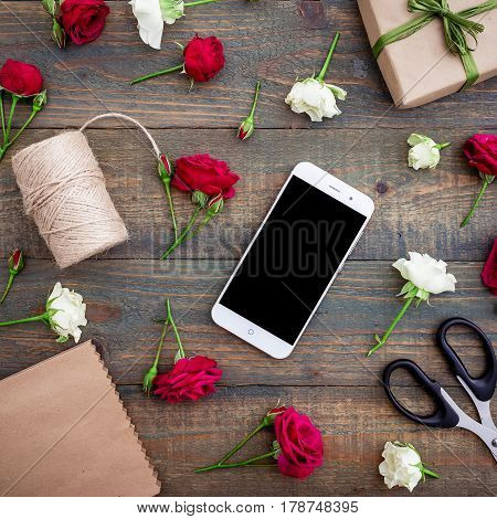 Mobile phone with roses, gift box and twine on wood background. Flat lay, top view workspace