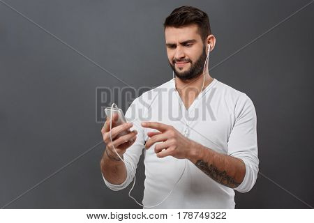 Displeased young handsome man in headphones looking at phone over grey background. Copy space.