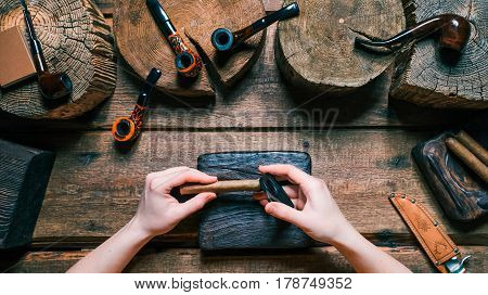 Human hands cutting cigar with cutter on dark board. Tobacco and pipes on wood. Close-up top view