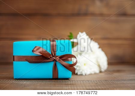 Wooden background with a gift and flowers. The concept of Mother's Day birthday March 8.
