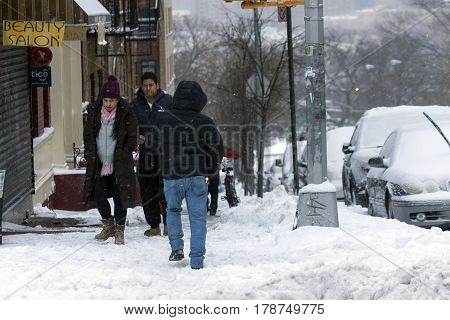 BRONX NEW YORK - MARCH 14: People walk along street during snow storm. Taken March 14 2017 in New York.