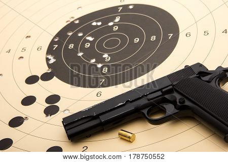 9 mm black pistol - handgun over paper target with hits - holes and empty cartridge shell