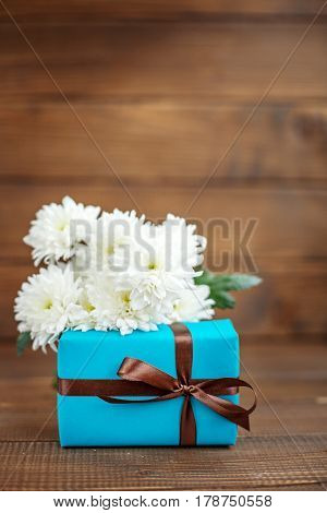 Wooden background with gift and white flowers for congratulations. The concept of Mother's Day birthday March 8.