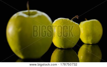 fresh red apple with droplets of water against black background diet, eat, food reflection drops