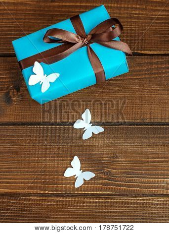 Wooden background with gift and butterflies. Top view. The concept of Mother's Day birthday March 8.