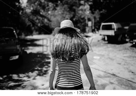 Woman in her back with hat walking away from the camera in the countryside.