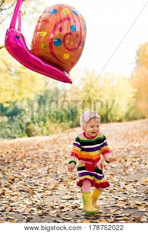 Portrait of happy little girl playing with air balloon in the park. Outdoors colorful autumn photo. Seasonal clothes. Childhood.
