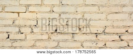 Panorama of old painted brick wall. Old bright brick wall texture. Brick wall painted in white