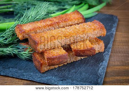 Fried bread croutons toasts and dill on a black stone board