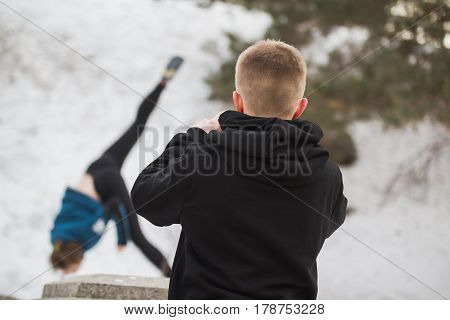 Teenager boy looking to acrobatic jump girl in winter city park - parkour concept, de-focused