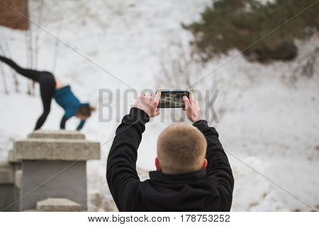 Teenager boy makes photo on smartphone of acrobatic jump girl in winter city park - parkour concept, de-focused