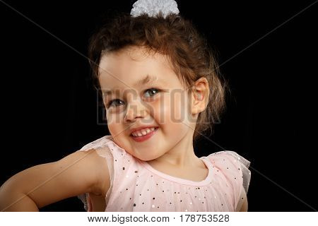 Close-up Portrait of 3 year old little girl with pink dress, shy on black background