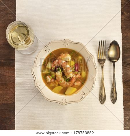 A square photo of a shrimp and potato dish with a glass of white wine, shot from above on a dark wooden texture with a place for text