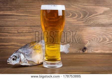 Fish and lager beer in glass on wooden background
