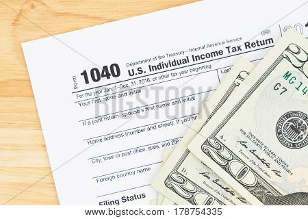 A US Federal tax 1040 income tax form with money on a wood desk