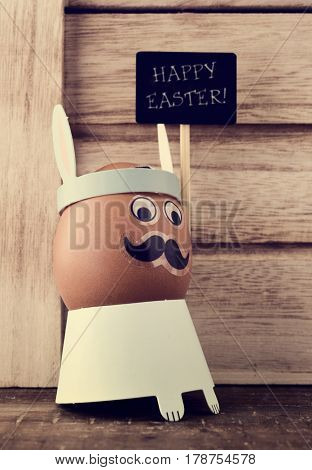 closeup of an easter egg decorated with eyes and a mustache, holding a black signboard with the text happy easter written in it, on a wooden rustic background